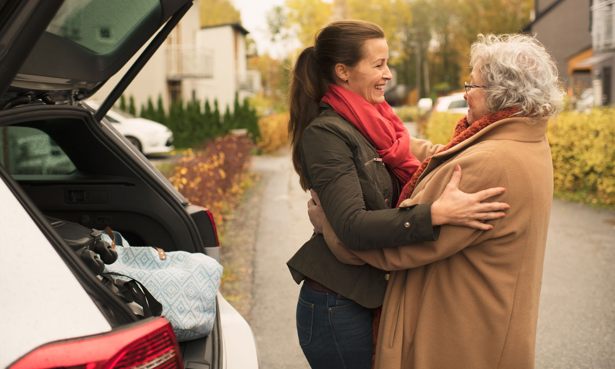 Older woman and younger woman hugging, saying goodbye in front of a car